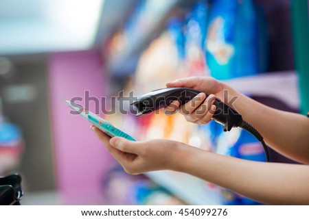 Closeup Woman's hand being held scanner within convenience stores .