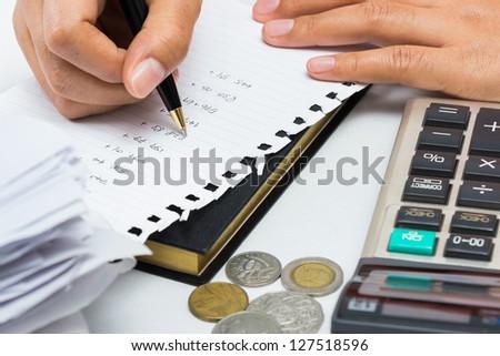 Closeup woman's hand calculating financial work - stock photo