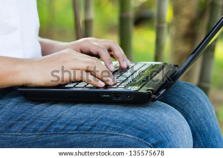 Closeup woman's hand using laptop on her lap