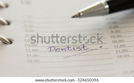 closeup words dentist on  notebook . soft focus - stock photo