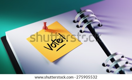 Closeup Yellow Sticky Note paste it in a notebook setting an appointment. The words Vote! written on a white notebook to remind you an important appointment. - stock photo