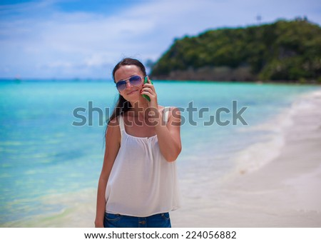 Closeup young beautiful woman at beach talking on her phone - stock photo