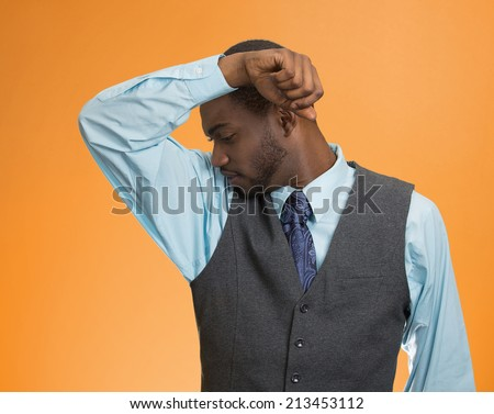 Closeup young man, smelling sniffing his armpit, something stinks bad, foul odor isolated orange  background. Negative human facial expressions, feeling body language, perception. Personal hygiene - stock photo