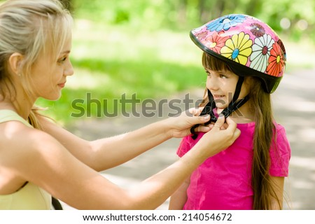 closeup young mother dresses her daughter's bicycle helmet - stock photo