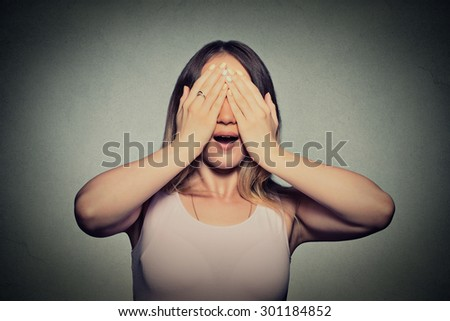 Closeup young woman covering her eyes with hands doesn't see  - stock photo