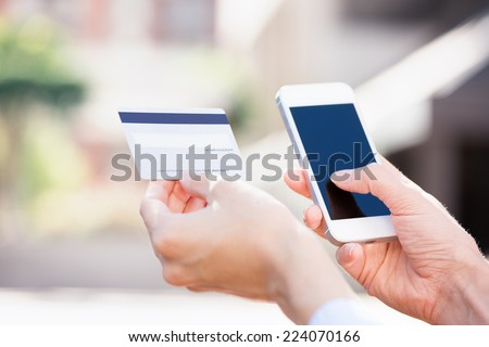 Closeup young woman hands holding credit card and using cell, smart phone for online shopping or reporting lost card, fraudulent transaction, isolated city outside background. New generation gadget - stock photo