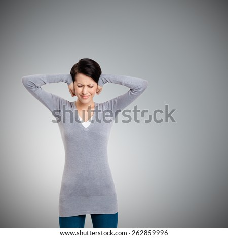 Closing ears with hands, isolated on grey - stock photo