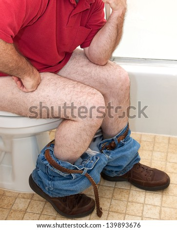 Closupe of a man thinking things over while sitting on the toilet. - stock photo