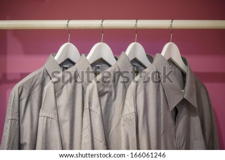 Cloth bar with shirts on curved hangers in wardrobe