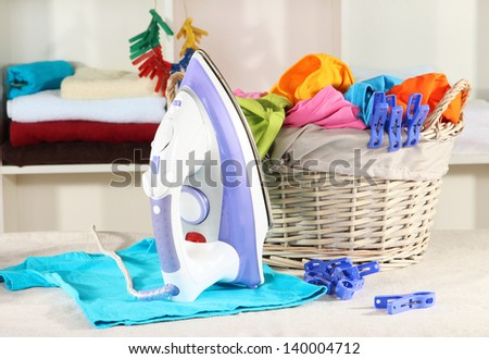 Clothes and iron on table on shelves background