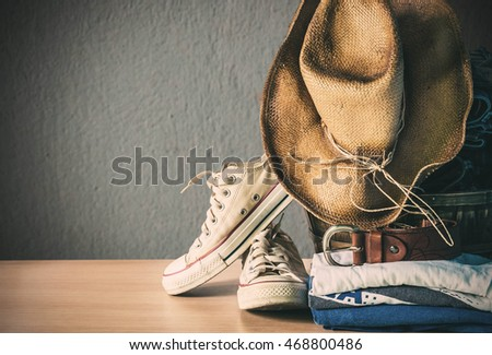 Clothes and old sneakers on a wooden floor.