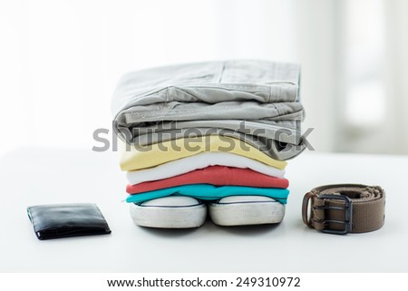 clothes and personal staff concept - close up of folded shirts, pants, belt, wallet and shoes on table at home - stock photo