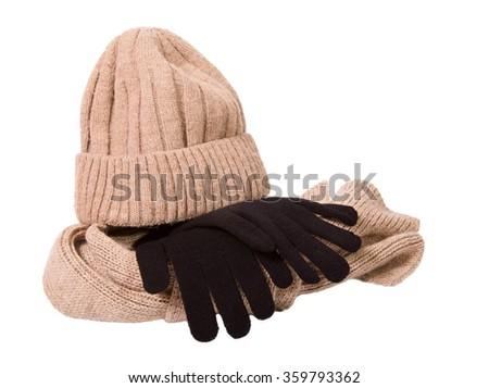Clothes for a cold season: woolen cap, scarf and gloves. Cap and scarf of beige color, glove black. The object is isolated on a white background - stock photo