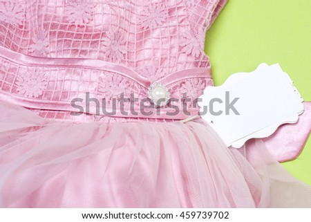 Clothes for newborn baby girl on light green background. Copy space for text
