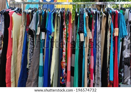 Clothes for sale at street market. Women's fashion. - stock photo