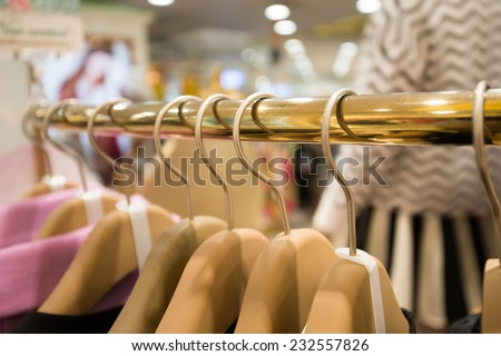 Clothes hang on a shelf in a designer clothes store - stock photo
