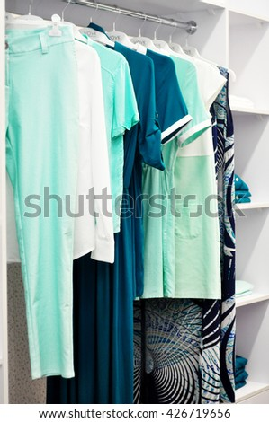 Clothes hang on a shelf in a designer clothes store.  Clothing store for women. Shop dresses. Clothes rack in shopping center. Dressing with complementary colors blue, yellow, orange, turquoise. - stock photo