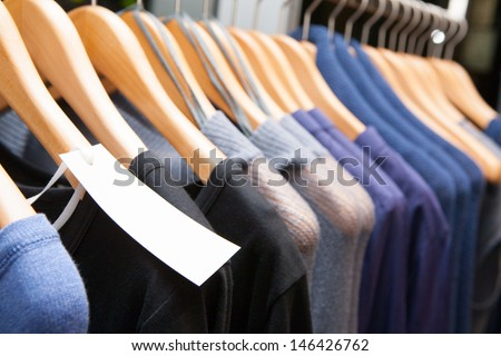 Clothes hang on a shelf in a designer clothes store in Melbourne, Australia - stock photo