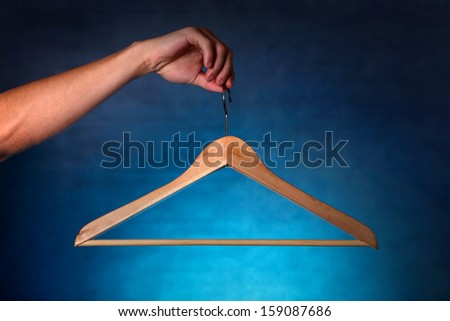 Clothes Hanger in a hand on the dark background - stock photo