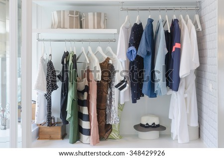 clothes hanging in closet with hat at home - stock photo