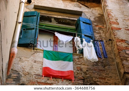 Clothes hanging to dry and Italian flag. Venice (Italy) - stock photo