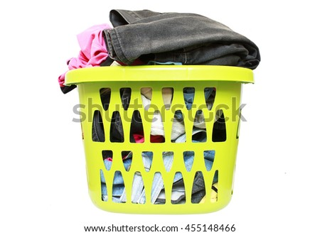 Clothes in a laundry green basket isolated on white background - stock photo