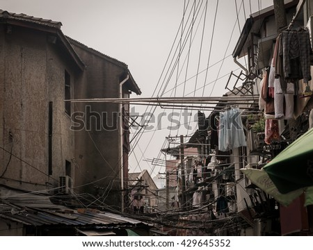 clothes in a traditional alley,Shanghai,china with residential buildings - Clothes line in a old street - Dramatic light - stock photo
