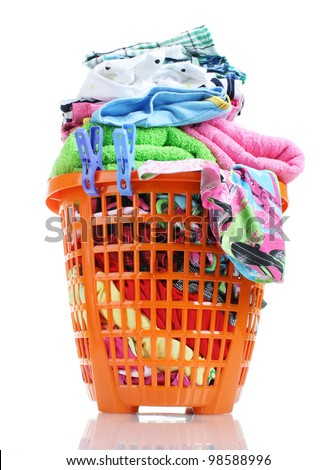 Clothes in orange plastic basket isolated on white - stock photo