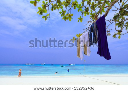 Clothes of tourism hang on tree branch, beach in south of Thailand