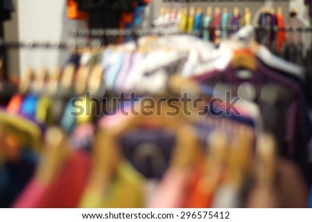 clothes on a rack on a flea market in bokeh. Defocus background - stock photo