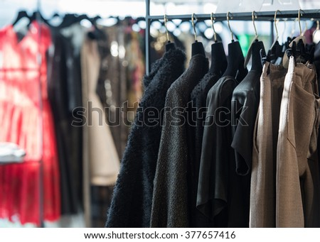 Clothes on hangers in a retail shop. - stock photo