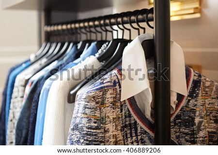 Clothes on hangers in shop. - stock photo