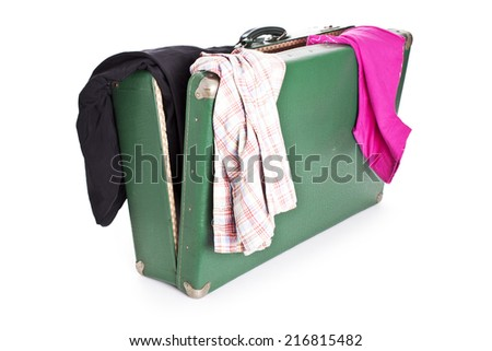Clothes on old suitcase isolated on white - stock photo