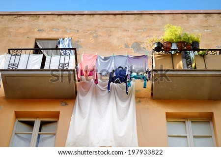 Clothes on the line along balconies in italian town - stock photo