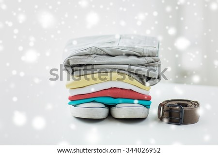 clothes, personal staff and objects concept - close up of folded shirts, pants, belt and shoes on table at home over snow effect - stock photo