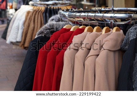 clothes rack with ladies winter jackets and coats for sale - stock photo