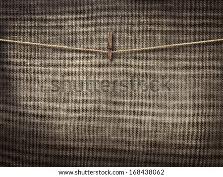 clothesline with clothespins on linen background - stock photo