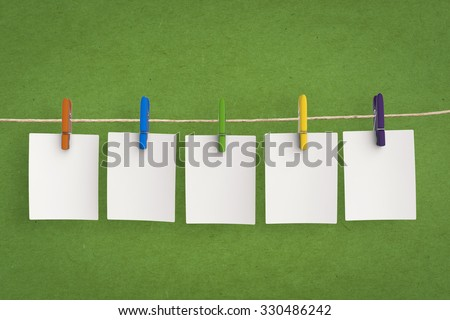 clothespin hanging with blank paper on green background