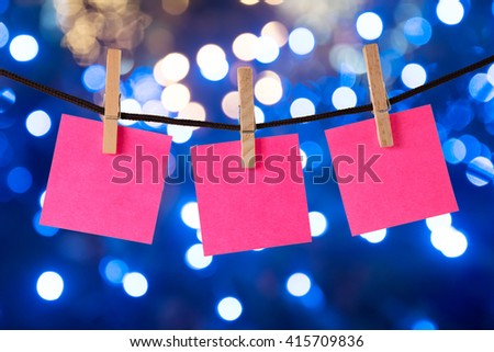 clothespin hanging with blank pink paper on blue abstract background  - stock photo