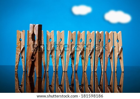 clothespin team in row with old leader on blue background - stock photo