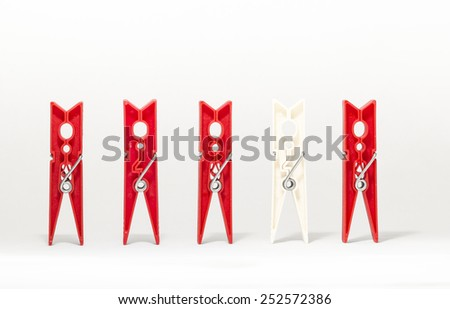 clothespins on white background representing differences of race - stock photo