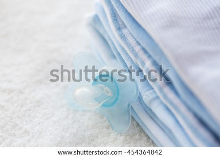 clothing, babyhood, motherhood and object concept - close up of baby soother and pile of clothes for newborn boy - stock photo