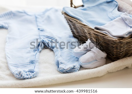 clothing, babyhood, motherhood and object concept - close up of white baby bootees with pile of clothes and towel for newborn boy in basket on table - stock photo