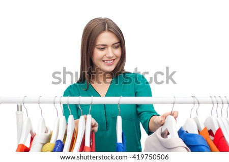 clothing, fashion, style and people concept - happy woman choosing clothes at home wardrobe