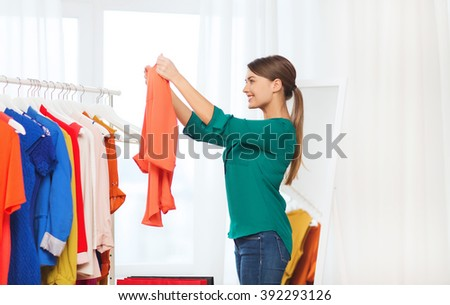 clothing, fashion, style and people concept - happy woman with shopping bags and clothes at home wardrobe