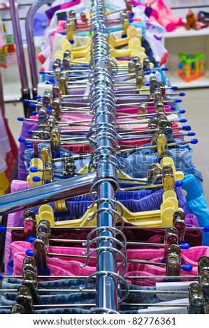 Clothing store. Rows of clothes on hangers - stock photo
