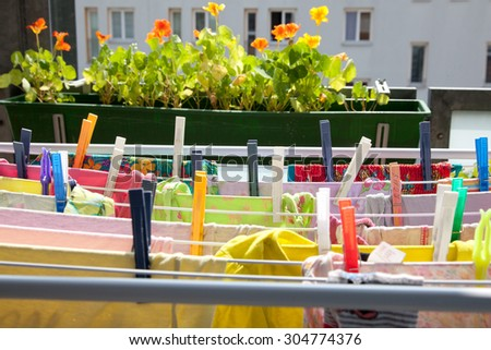 clothing with clothespins on clothes horse on a balcony in summer  with flowers in the background.
