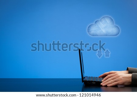 Cloud computing concept - man working with laptop and cloud represented by icon. Blank negative space for your texts and design on left. - stock photo