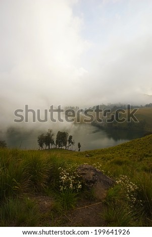 Cloud entering Ranu Kumbulo Lake, 1st campsite at Semeru Volcano Mountain, East Java, Indonesia. Semeru Mountain also known as Mahameru Mountain in Indonesia means the great mountain.  - stock photo