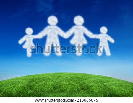 Cloud in shape of family against green hill under blue sky